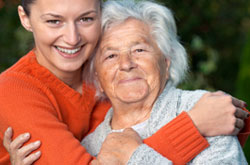 Photograph of an elderly woman being hugged by a younger woman.